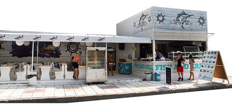 Поглед към ресторанта от този ъгъл За откриването на ресторант Mr. Fish в курортното градче Китен, ни потърсиха собствениците на обекта с идеята да реализираме автентичен бранд лесно разпознаваем и запомнящ се. може да се забележи дизайна на рекламното пано поставено над заведението и част от интериора на обекта изготвен от Muse Creativity